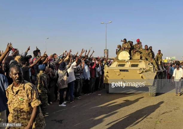 Sudanese protesters flash the victory sign at a passing military vehicle as they rally for a second day outside the military headquarters in the...