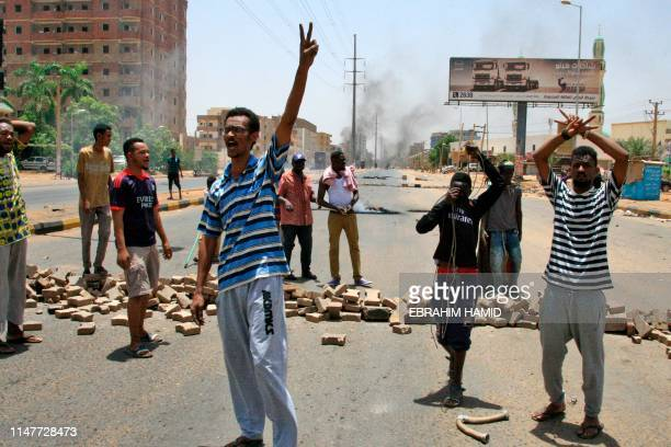Sudanese protesters gesture and chant slogans outside Khartoum's army headquarters on June 3, 2019 after security forces broke up a weeks-long...