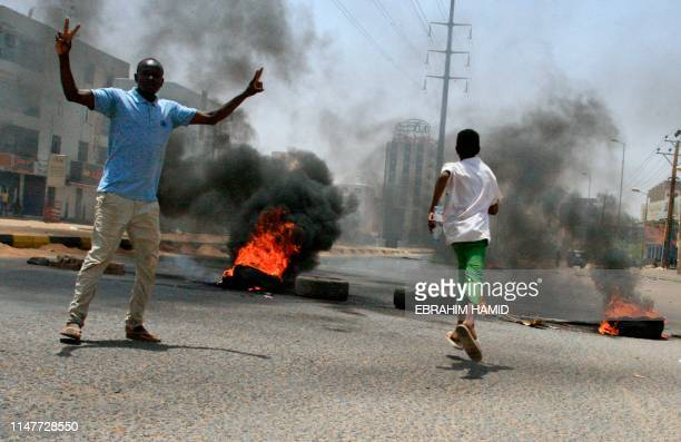 Sudanese protesters gesture as smoke billows from burning tyres near Khartoum's army headquarters on June 3, 2019 after security forces broke up a...