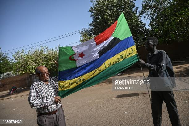 Sudanese protesters hold a banner displaying algerian and Sudanese national flags during a sitin outside the army headquarters in the capital...