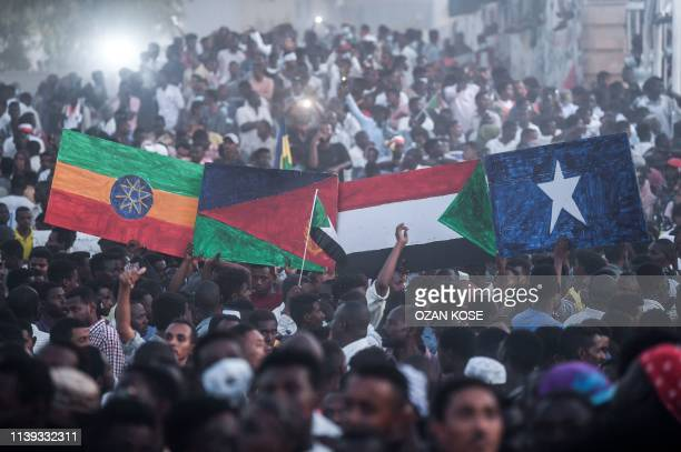 """Sudanese protesters hold national flags of Ethiopia, Eritrea, Sudan and Somalia as they gather for a """"million-strong"""" march outside the army..."""