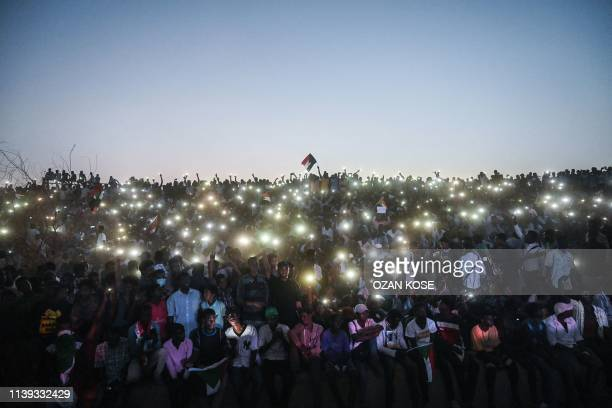 "Sudanese protesters open their smartphones lights as they gather for a ""million-strong"" march outside the army headquarters in the capital Khartoum..."