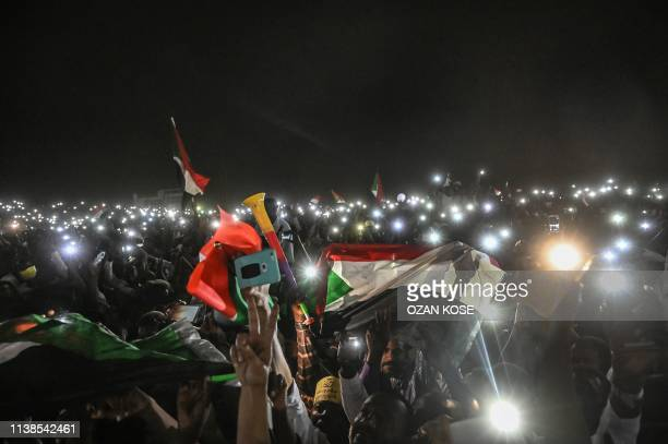 Sudanese protesters open their smartphones lights during a protest outside the army headquarters in the capital Khartoum on April 21, 2019. -...