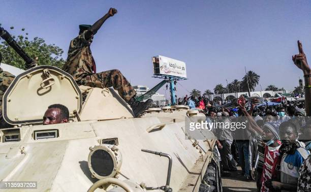 Sudanese protesters salute a military armoured vehicle as they gather during a demonstration in front of the military headquarters in the capital...