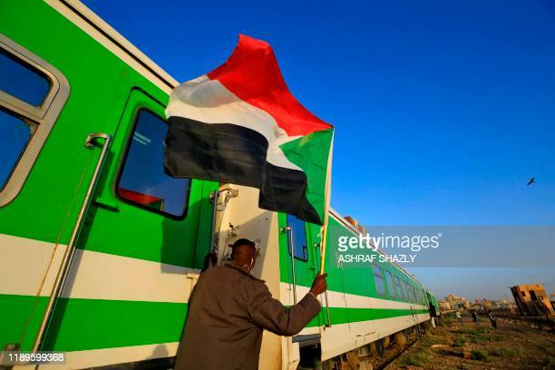 Sudanese protesters wait at a train station in Khartoum to board a train to Atbara on December 19, 2019 to celebrate the one-year anniversary of...