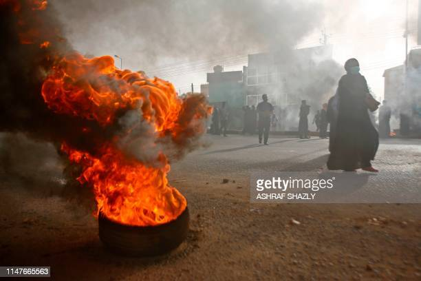Sudanese protesters walk past burning tyres as military forces tried to disperse a sit-in outside Khartoum's army headquarters on June 3, 2019. - At...