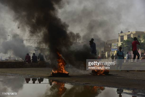 Sudanese protesters walk past burning tyres during a demonstration in Khartoum's twin city of Omdurman on June 3 2019 At least five protesters were...