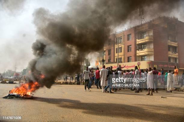 Sudanese protesters walk past burning tyres during a demonstration in Khartoum's twin city of Omdurman on June 3, 2019. - At least five protesters...