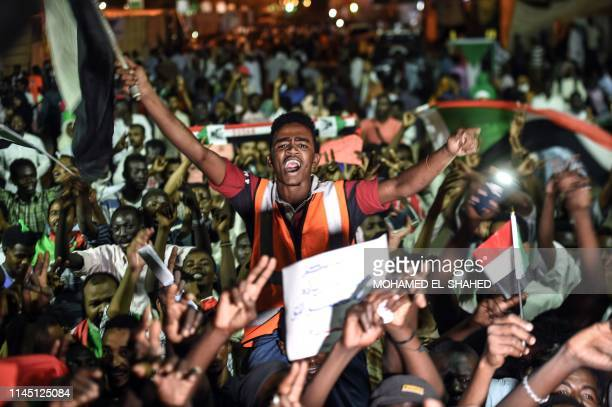 TOPSHOT Sudanese protesters wave flags and flash victory signs as they gather for a sitin outside the military headquarters in Khartoum on May 19...
