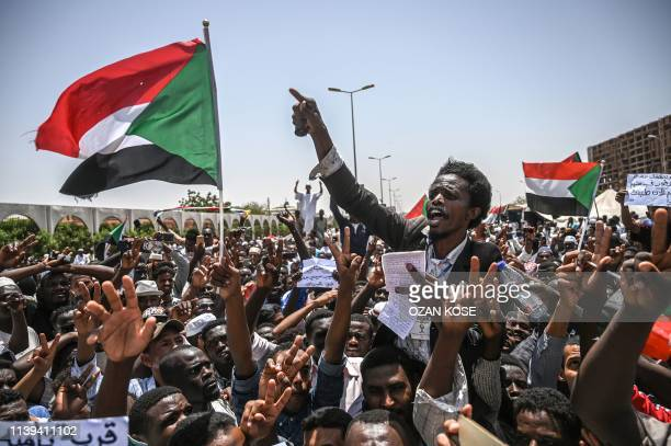 TOPSHOT Sudanese protesters wave national flags as they chant slogans during an a sitin outside the army headquarters in the capital Khartoum on...