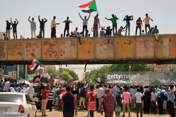Sudanese protesters waving a national flag take part in a sitin outside the army headquarters in Khartoum on May 5 as thousands of people remain...