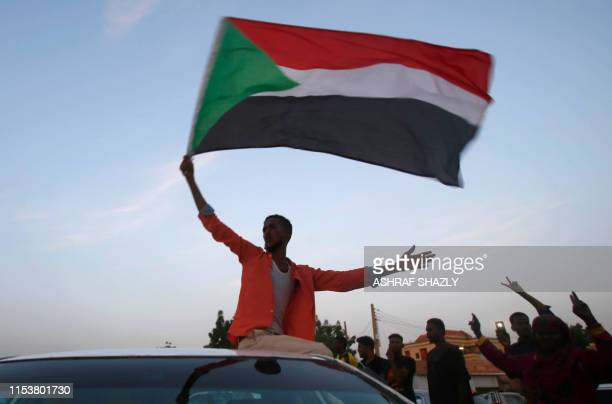 TOPSHOT Sudanese protestors celebrate in the streets of Khartoum after ruling generals and protest leaders announced they have reached an agreement...