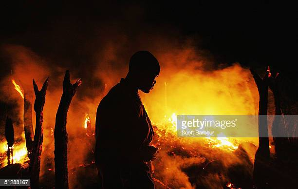 Sudanese rebel fighter from the Justice and Equality Movement sombrely watches the abandoned village of Chero Kasi burn less than an hour after...