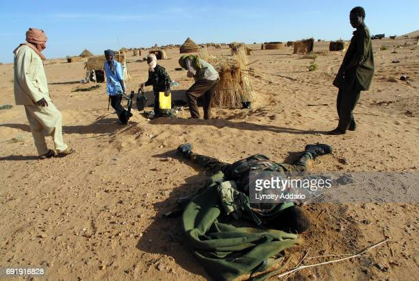 Sudanese rebels with the NRF pick up ammunition and weapons from beside a dead Sudanese government soldier as the rebels walk through a temporary...