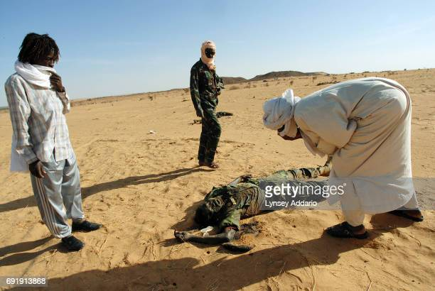 Sudanese rebels with the NRF try to read the nametag of a dead Sudanese government soldier as they walk through a temporary military camp for the GOS...