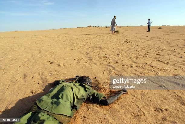 Sudanese rebels with the NRF walk past a dead Sudanese government soldier as they walk in the desert near a temporary military camp for the GOS near...