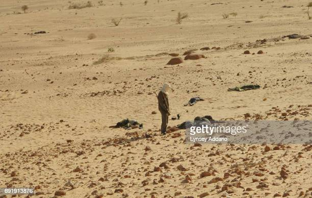 Sudanese rebels with the NRF walk past dead Sudanese government soldiers as they walk through a temporary military camp for the GOS near the Darfur...