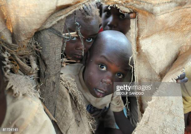 Sudanese refugee children from Darfur peer from a hole in their shelter at the Farchana refugee camp that has more than 20000 Darfur refugees on June...