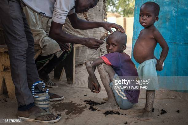 Sudanese refugee children receive an haircut in Treguine camp in Hadjer Hadid in the Ouaddaï region in eastern Chad on March 24 2019 Since 2003 and...
