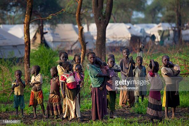Sudanese refugee children stand near their tents in a muddy field July 15 2012 in Jamam refugee camp South Sudan Up to 16000 refugees are in the...