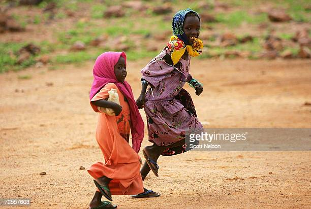 Sudanese refugee girls from the Darfur region of Sudan run home after attending a UNICEF school in the Farshana refugee camp August 29 2004 in...