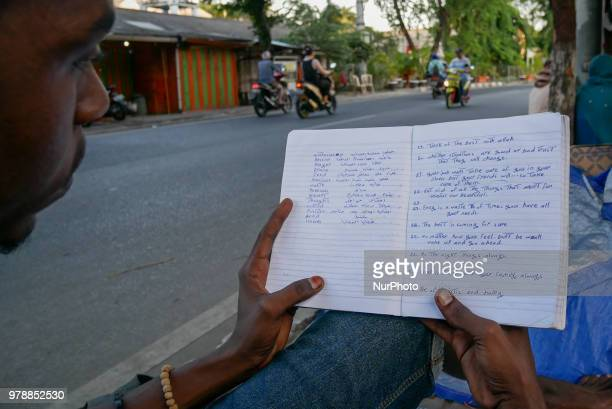 A Sudanese refugee learns an english as he settling on the roadside in front of the overcapacity immigration detention house in Jakarta Indonesia on...