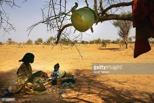 Sudanese refugee mother who fled with her five children from the Darfur region of Sudan weaves baskets with her daughter at her temporary home under...