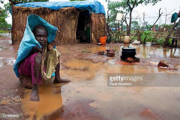 Sudanese refugee sits outside her hut on a rainy afternoon at the Yida refugee camp, along the border with North Sudan July 5, 2012 in Yida, South...