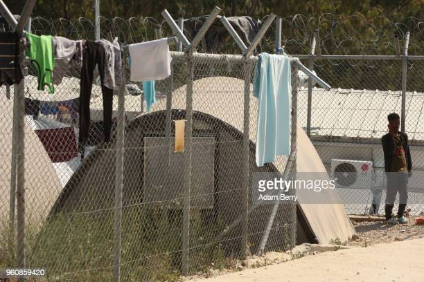 Sudanese refugee speaks on his mobile phone next to clothing drying next to a tent at the Moria refugee camp on May 20 2018 in Mytilene Greece...