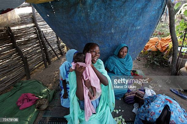Sudanese refugee woman tends to her baby in their shelter on November 8 2006 in the Goz Amer Refugee Camp Chad Since 2004 refugees have fled from...