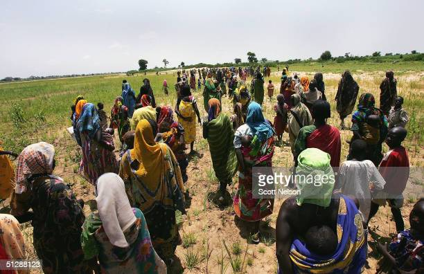 Sudanese refugees from the violence plagued Darfur region flee across an intermittent stream marking the international border with neighbouring Chad...