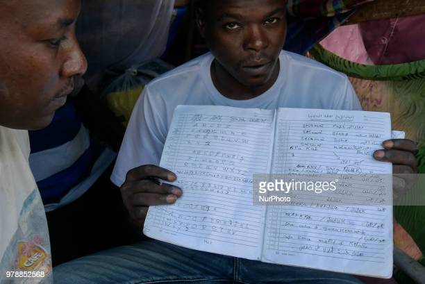 A Sudanese refugees learn an language book as he settling on the roadside in front of the overcapacity immigration detention house in Jakarta...