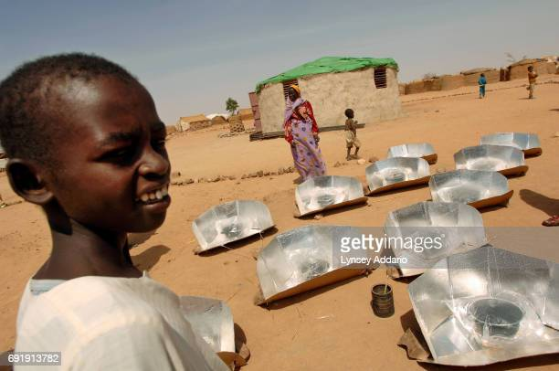 Sudanese refugees stand around solar stoves in a training session led by Scientist Derk Rijks from the Netherlands in Iridimi camp in northeastern...
