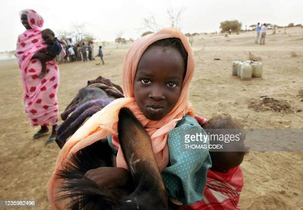Sudanese refugees walk to their camp after they collected some water in a well at the Sudan-Chad border in Abulu Kore, Eastern Chad 28 June 2004 Some...