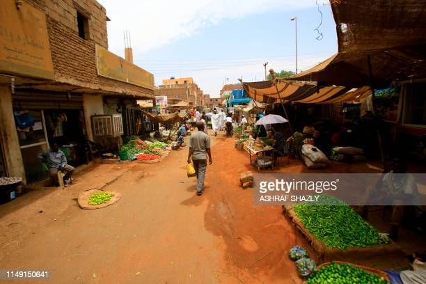 Sudanese residents walk in the central market of Khartoum on June 10 as most of the shops and businesses remained shut. - Residents generally stayed...