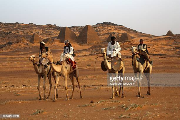Sudanese ride their camels near ancient pyramids in the area of Bejrawiya near the hometown of Sudanese President Omar alBashir on April 1 2015 AFP...