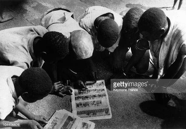 Sudanese schoolchildren reading the French magazine COEURS VAILLANT together in the 1950's