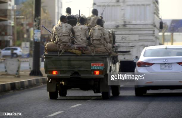 Sudanese security forces ride in the back of a pick up truck through a main avenue in Khartoum as the military continued to disperse protesters by...