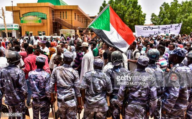 TOPSHOT Sudanese security forces stand by as demonstrators march with a national flag outside a courthouse complex in the Sudanese capital's twin...