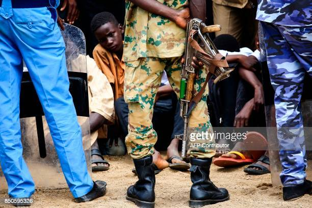 A Sudanese soldier carries a Kalashnikov assault rifle while standing guard during a speech given by President Omar alBashir in Nyala the capital of...