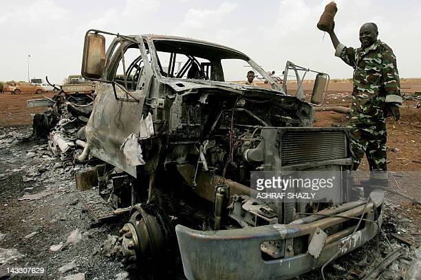 A Sudanese soldier walks next to a damaged vehicle at the airport of Sudan's main petroleum centre of Heglig on April 23 2012 Sudanese President Omar...