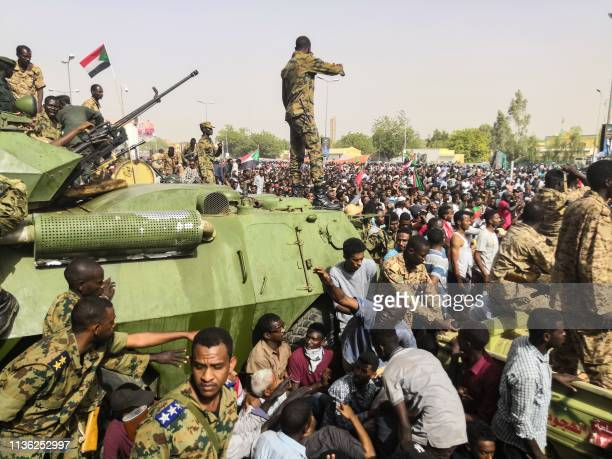 TOPSHOT Sudanese soldiers stand guard on armoured military vehicles as demonstrators continue their protest against the regime near the army...