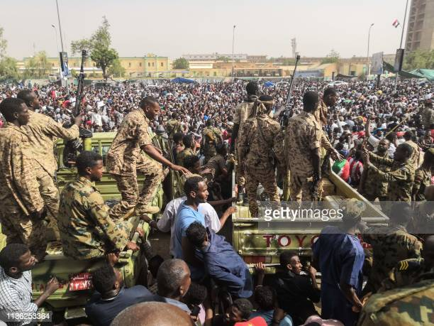 Sudanese soldiers stand guard on armoured military vehicles as demonstrators continue their protest against the regime near the army headquarters in...