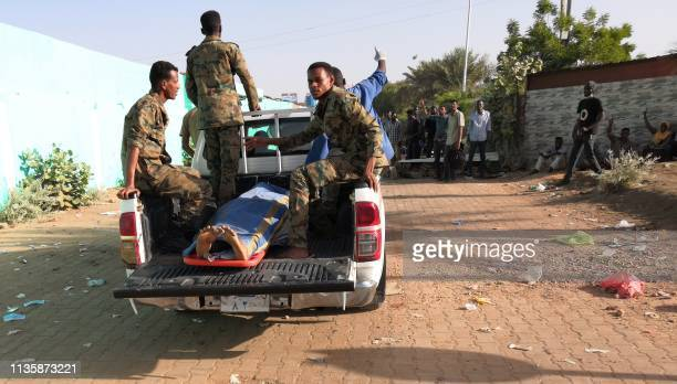 Sudanese soldiers transport a body covered in cloth in a pick-up truck from the area around the military headquarters in the capital Khartoum during...
