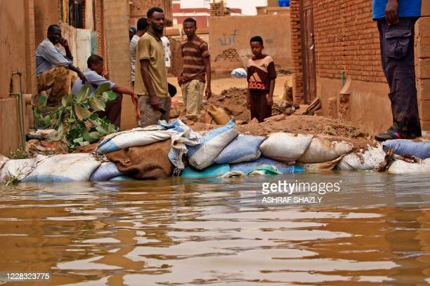 Sudanese stand amidst flood waters in Tuti island, where the Blue and White Nile merge between the twin cities of the capital Khartoum and Omdurman,...