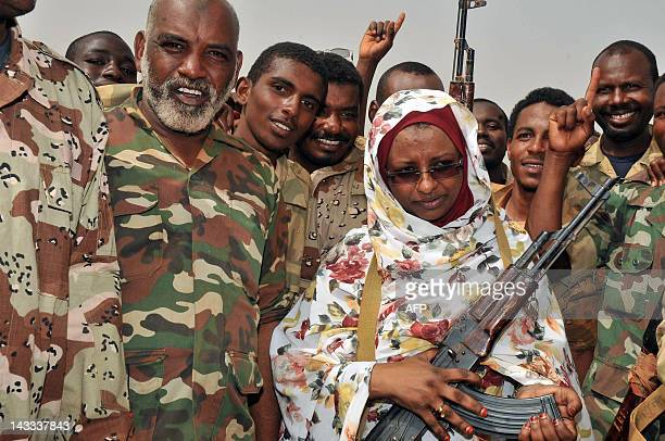 Sudanese State Minister of Information Sana Hamad holds a gun as she poses with Sudanese soldiers in the oil town of Heglig on April 24 2012 South...