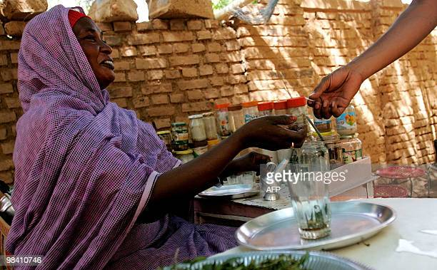 Sudanese street vendor sells a cup of tea to a customer in Khartoum on April 12 2010 Sudanese nationwide are voting for president as well for...