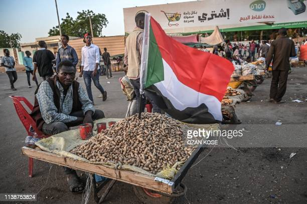 Sudanese street vendor waits for customers during a protest outside the army headquarters in the capital Khartoum on April 22, 2019. - Sudan's new...
