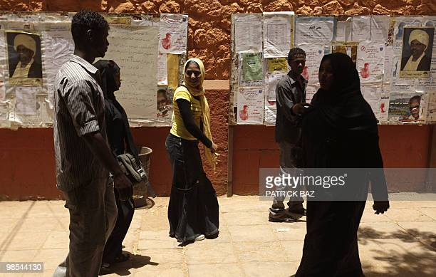 Sudanese students walk past electoral campaign posters of President Omar alBeshir at the campus of AlNeelain University in Khartoum on April 18 2010...