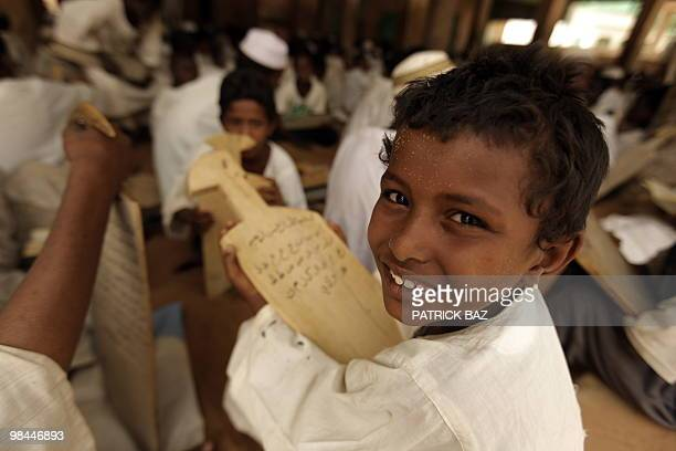 A Sudanese Sufi student holds his wooden board or Lawha as he recites verses of the Koran at the Qadiriya Badiriya Sufi mosque in the village of Umm...